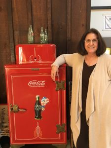 Christine seen here in our office by the antique Coca Cola Machine